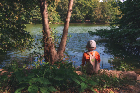 Small child sits in the forest near the pond and enjoys the beautiful nature.