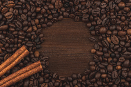 Roasted coffee beans and cinnamon sticks. Background, close-up view. 스톡 콘텐츠