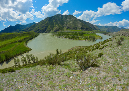 Landscape in the mountain area in Altai region (Russia) with a mountains, steppe, rocks, the Katun river, little village, sky with clouds and jalama bands on bushes as a foreground. photo