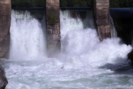 espumante: Antiguo (1930) la planta de energ�a hidroel�ctrica retro vendimia en el r�o Chemal (territorio de Altai, Siberia, Asia Central, Rusia) para la generaci�n de electricidad industrial. El r�o, el flujo del agua de espuma con gas y la presa son visibles. Foto de archivo