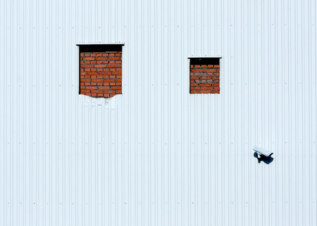 Abstract : wall of modern building with white siding, two windows bricked up with red bricks and security video camera. Can be used as a wallpaper. photo