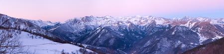 alight: Panorama. La mattina invernale nella zona di montagna nel Arkhyz (Russia) con pendii coperti di neve, cima di vette scendere dalla luce del sole e cielo blu rosa un Archivio Fotografico