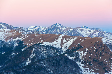 alight: The winter morning in the mountain area in Arkhyz (Russia) with slopes covered by snow, top of peaks alight by sunlight and blue pink sky