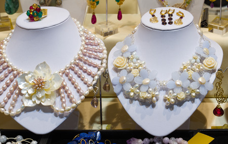 perls: Jewellery storefront (shopwindow) with decorations: colorful beads and necklaces of gems, perls and different stones.