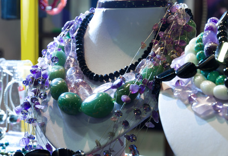 shopwindow: Jewellery neclace of colorful stones on mannequins in the shopwindow. Stock Photo
