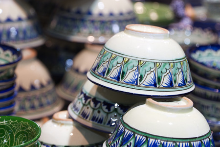 Handmade traditional national uzbek kyrgyz or kazakh ceramics crockery (piala, tea bowls, ware, things ) made of clay on the shopboard at the flea market in Moscow (Russia). Stock Photo