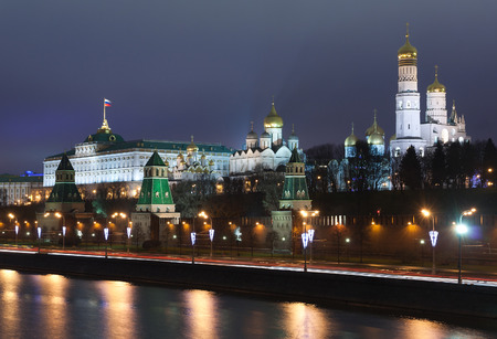 moskva river: Touristic spot in the Moscow center (landmark): view to the Kremlin with wall and towers, Moskva river, embankment by a winter night at Christmas time with streetlight illumination and reflectiobs in the water.