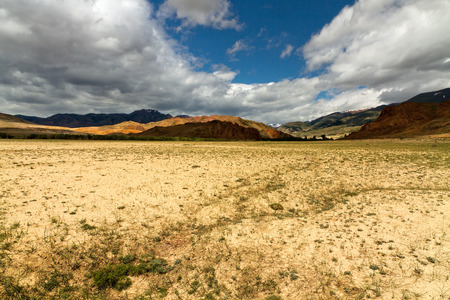 russia steppe: The Altai landscape (Russia) with a steppe or semi desert, red mountains at horizon and blue sky with clouds. Stock Photo