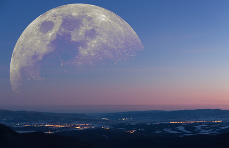 moon  metropolis: Fantastic landscape: the winter early morning view from the mountains to a valley with towns emitting light with huge arising moon. Stock Photo
