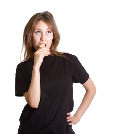 gozinaki: Portrait of an attractive beautiful thoughtfu young caucasian woman  lady  girl  female  model dressed in black t-shirt, eating  sesame brittle or brittle candy or nut brittle (which all are English names for a georgian sweet gozinaki or kozinaki) and Stock Photo