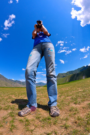 fish eye lens: Portrait of nature photographer woman taking landscape pictures in the mountain area (Altai, Russia). Shot was done with a fish eye lens. Stock Photo