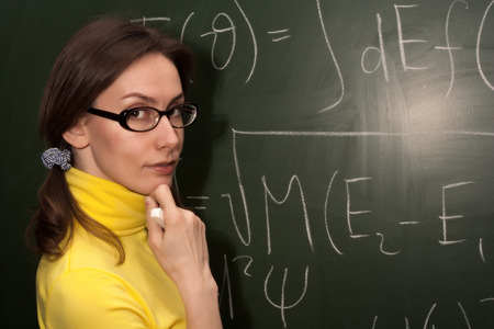 formulae: Portrait of an attractive beautiful pretty cute young brown haired caucasian woman (lady, girl, female, person, model) school teacher (professor or student in university or college) in glasses (spectacles, specs) who is standing thoughtfully at the chalk