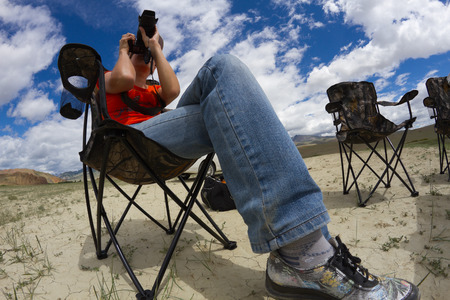 fish eye lens: Portrait of young woman nature photographer taking landscape pictures in the desert area (Altai, Russia). Shot was done with a fish eye lens.