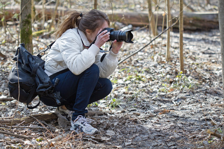 well equipped: Portrait of well equipped nature photographer young woman. The girl takis images in a spring day sunny forest.