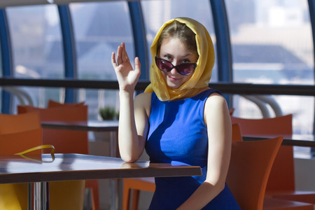Portrait of an attractive brown haired beautiful pretty cute young caucasian woman (girl, female, person, model) in blue dress, sunglasses and yellow headscarf sitting at a table in cafe, smiling and waving her hand greeting somebody in a gallery in airpo photo