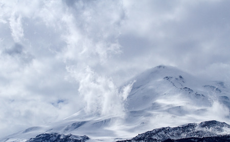 elbrus: Elbrus mountain (one of the highest mountain in the Caucasus region) covered by snow with clouds over it.