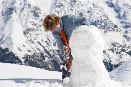 succesful: Nice looking pretty blonde caucasian happy cheerful succesful girl staying at the top of mountain covered by snow and making snowman.