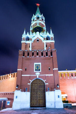 Moscow landmark: Spasskaya tower - the principal entrance to Kremlin by night with cloudy sky as a background. Portrait orientation. Stock Photo