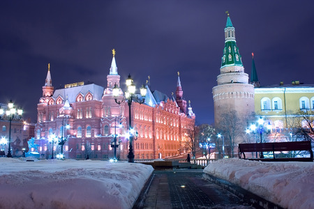 moscow: An alley at the Manege square (Manezhnaya ploshchad) in Moscow at a winter evening with snowdrifts on its sides and a  view on the State Historical Museum, the Alexander Garden and Kremlin wall and towers. Cloudy sky serves as a background. landscape orie