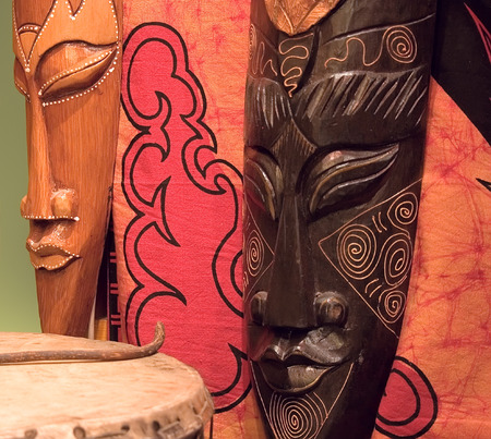 devotions: Two african wooden masks, tomtom and red painted fabric. Stock Photo
