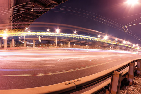 trails of lights: Anstract transportation photo: road (street, highway) by night with a bridge (flyver, overpass, interchange), traffic headlight trails and street lamps (lights) Stock Photo