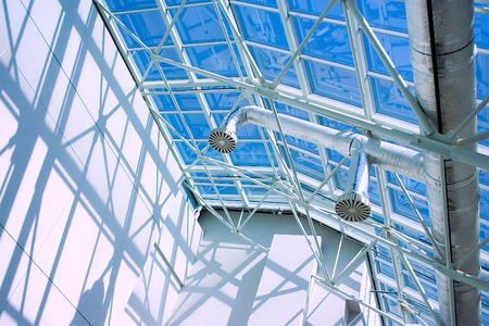 tubing: Glassy roof of contemporary business style  building with ventilation tubing, blue sky, sunlight and shadows and light playing.