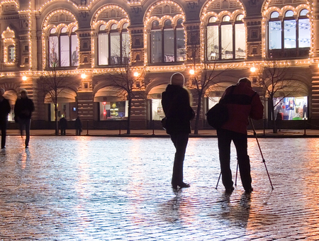 streetlights: Two photographers (man and woman) at the Red Square in Moscow by a winter night, flagging illuminated by streetlights.