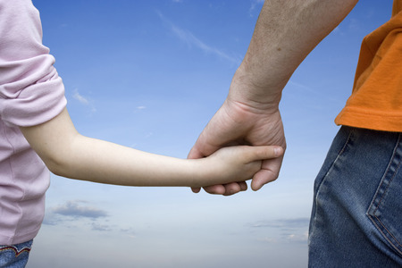 adult hand: Child and adult (parent or father) holding hands with blue sky and clouds as a background.