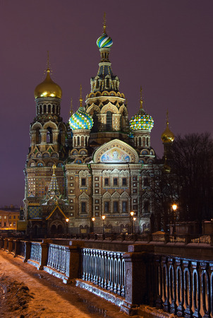streetlights: Russian landmark in Saint-Petersburg at winter night: orthodox cathedral (church) Spas-na-Krovi (Savior-on-Blood) at the embankment of Griboedov (Korm) channel (canal) covered by ice (snow) with streetlights, buildings and reflections