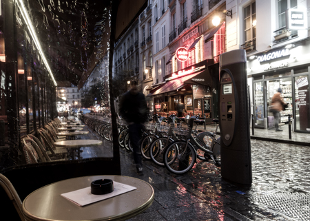 street lamp: Narrow Paris street near the city center at the rainy autumn evening. Empty cafe, bicicles for rent and little shops are visible.