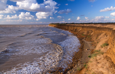 Landscape of the Sea of Azov by a windy summer evening. Waves on the water surface, blue sky with clouds, high coast.