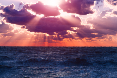 Vibrant sunset on the sea with waves on the water surface, clouds on the sky and sun rays. All this makes a specific nature pattern.