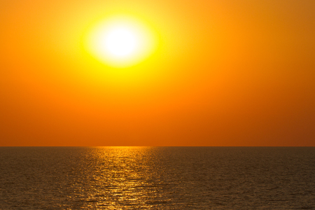 specific: Vibrant sunset on the sea with waves on the water surface, sun and orange sky. All this akes a specific nature pattern. Stock Photo
