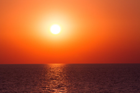 Vibrant sunset on the sea with waves on the water surface, sun and orange red  sky. All this akes a specific nature pattern.