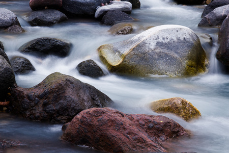 Nature detail: water stream which goes among big stones. Stock fotó
