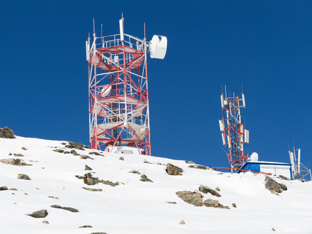 A group of communication antennas at a hill by winter day with blue sky in background. Stock Photo