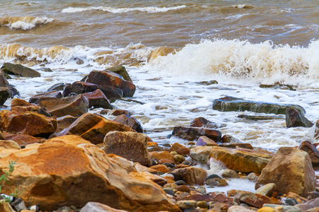 Nature scene: surf on the sea cost with waves and stones.