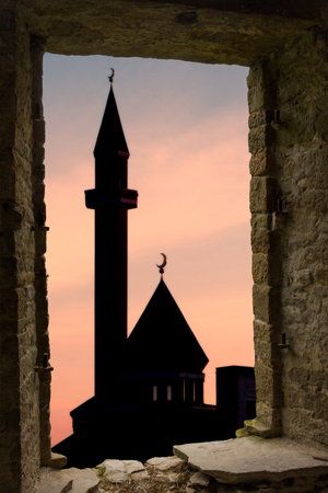 Islam religion abstract background: mosque silhouette against sunset sky background with clouds visible through ancient stone window. Stock Photo