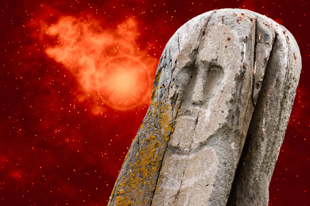 Ancient stone ritual idol (totem) with a universe image - space, stars, nebula, supernova explosion - as a background.