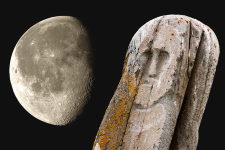 Stone ancient ritual tribal totem (idol) on dark background and Moon with surface details. Stock Photo