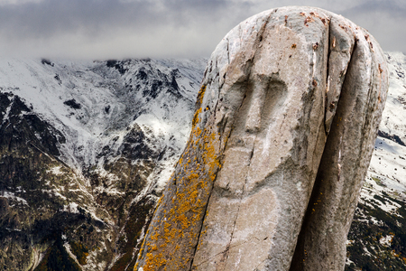 Ancient stone tribal ritual totem (idol) with a winter mountain landscape as a background.