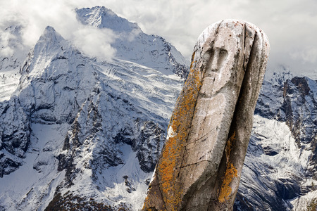 shamanism: Ancient stone tribal ritual totem (idol) with a winter mountain landscape as a background.