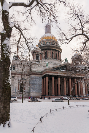 Old historical architecture landmark and touristic spot in Saint Petersburg, Russia: Saint Isaac's Cathedral and a park and street in front of it by a winter day with cars and trees covered by snow. Фото со стока