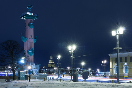 Old historical architecture landmark and touristic spot in Saint Petersburg, Russia: the Spit of the Vasilievsky island by a winter night with the rostral column and Saint Isaac's Cathedral visible far away.