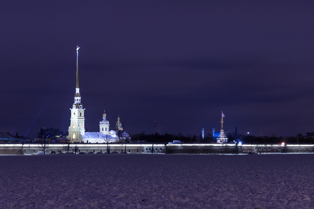 dom: Touristic landmark in Saint Petersburg, Russia: Peter and Paul fortress and Cathedral illuminated by a winter night with the Neva river covered by ice and snow in front of it and cloudy sky as a background.