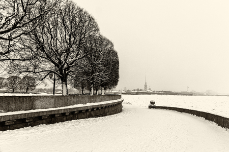 Llandmark in St Petersburg, Russia: Spit of Vasilievsky Island covered by snow by winter day with trees and Peter and Paul fortress and dom at the horizon. Black and white retro photo.
