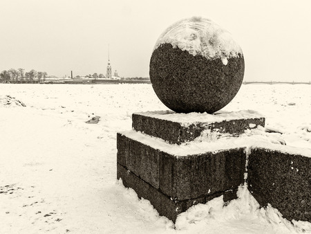 Landmark in St Petersburg, Russia: Spit of Vasilievsky Island  by winter day with granite sphere, Peter and Paul fortress at the horizon and Neva river in ice. Black and white retro photo