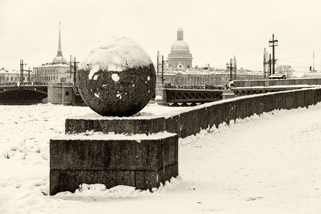 Landmark in St Petersburg, Russia: Spit of Vasilievsky Island  by winter day with granite embankment, the Palace bridge, old city and the Neva river in ice. Black and white retro photo. Фото со стока