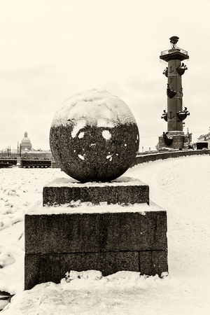 Landmark in St Petersburg, Russia: Spit of Vasilievsky Island by winter day with rostral column, granite embankment with sphere and the Neva river in ice. Black and white retro photo.