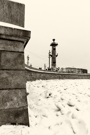 Landmark in St Petersburg, Russia: rostral column on the Vasilievsky Island by winter day with the Neva river covered by ice and snow and granite embankment. Black and white retro photo. Фото со стока